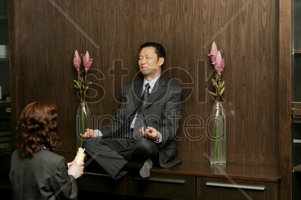 woman worshipping a businessman who is sitting on the shelf meditating stock photo