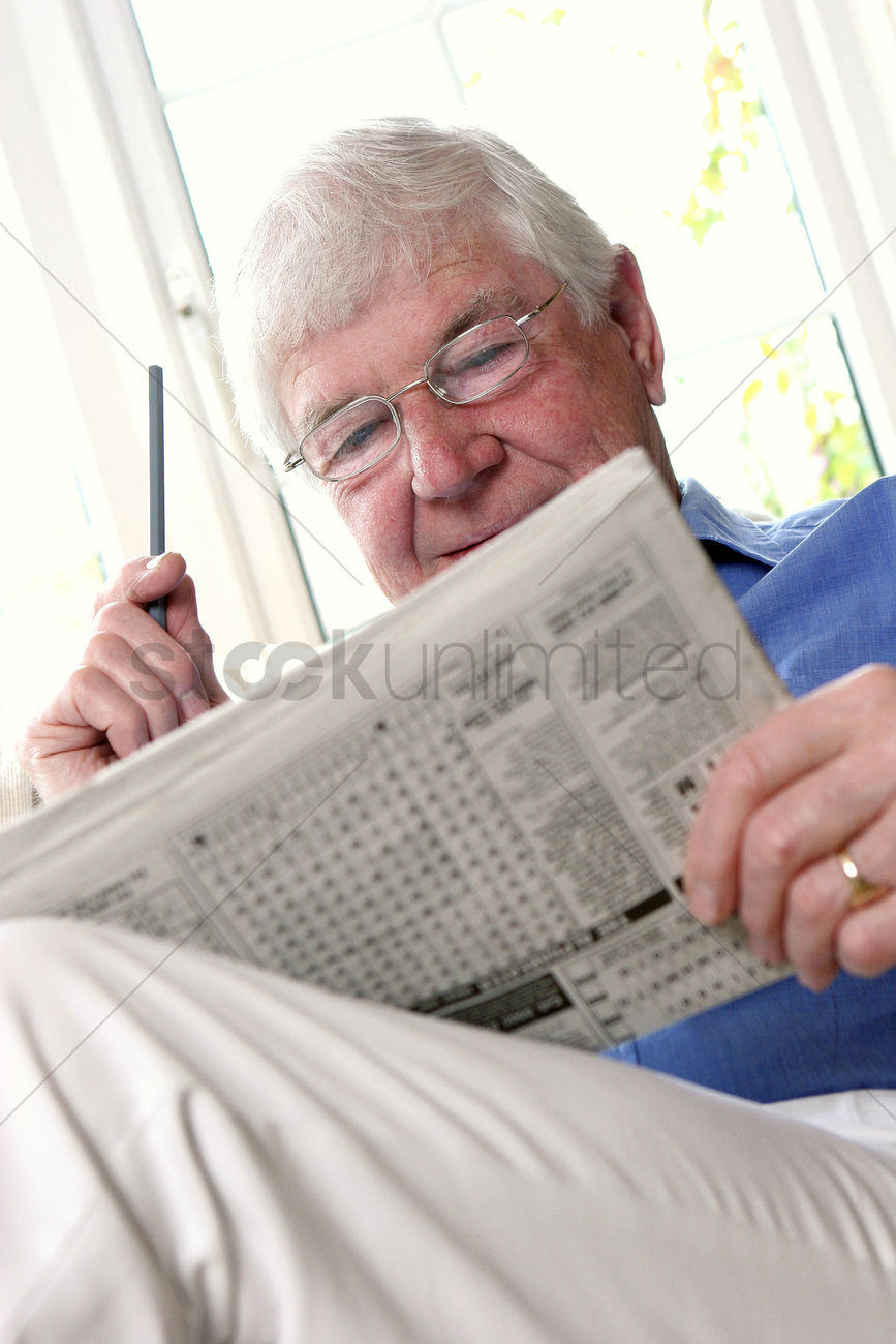 a bespectacled old man sitting on the couch reading newspaper stock