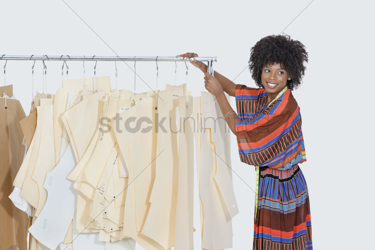African american female designer with sewing patterns on clothes african american female designer with sewing patterns on clothes rack over gray background stock photo jeuxipadfo Images