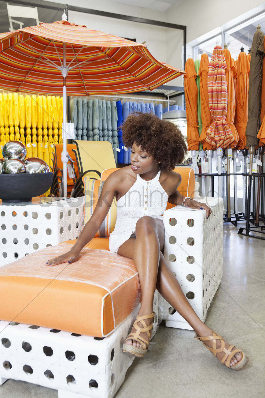 African American Woman Sitting In Arm Chair At Garden Furniture Store Stock  Photo