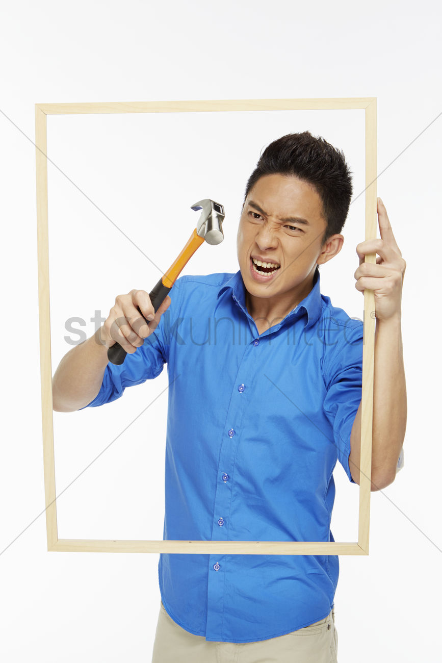 Angry man hitting a picture frame with hammer stock photo for Pictureframes net