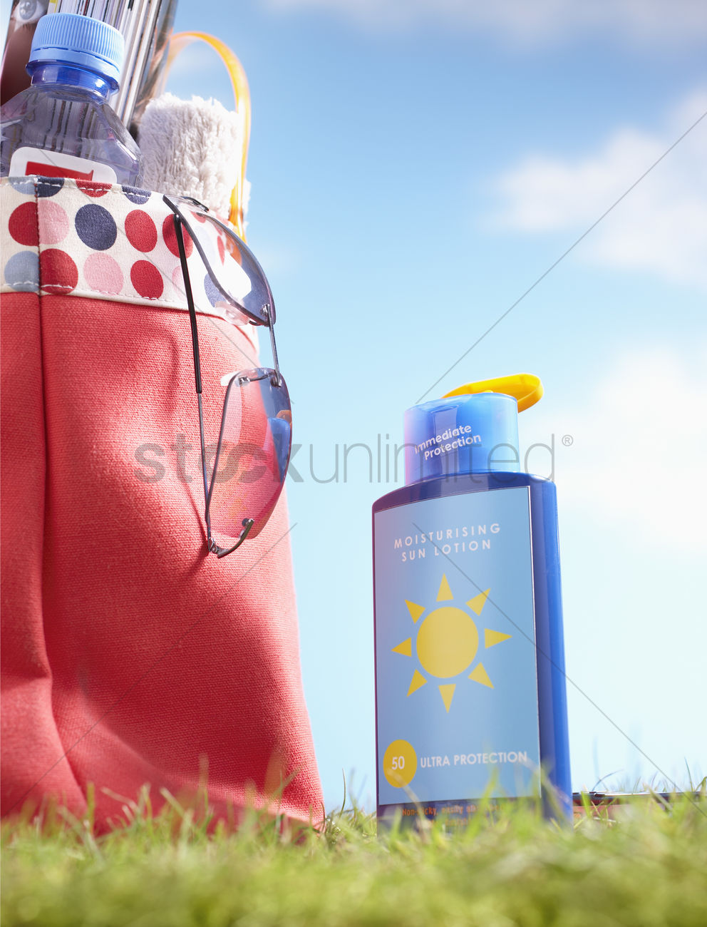 Bottle Of Suntan Lotion And Bag With Beach Items In Grass Close Up Stock Photo