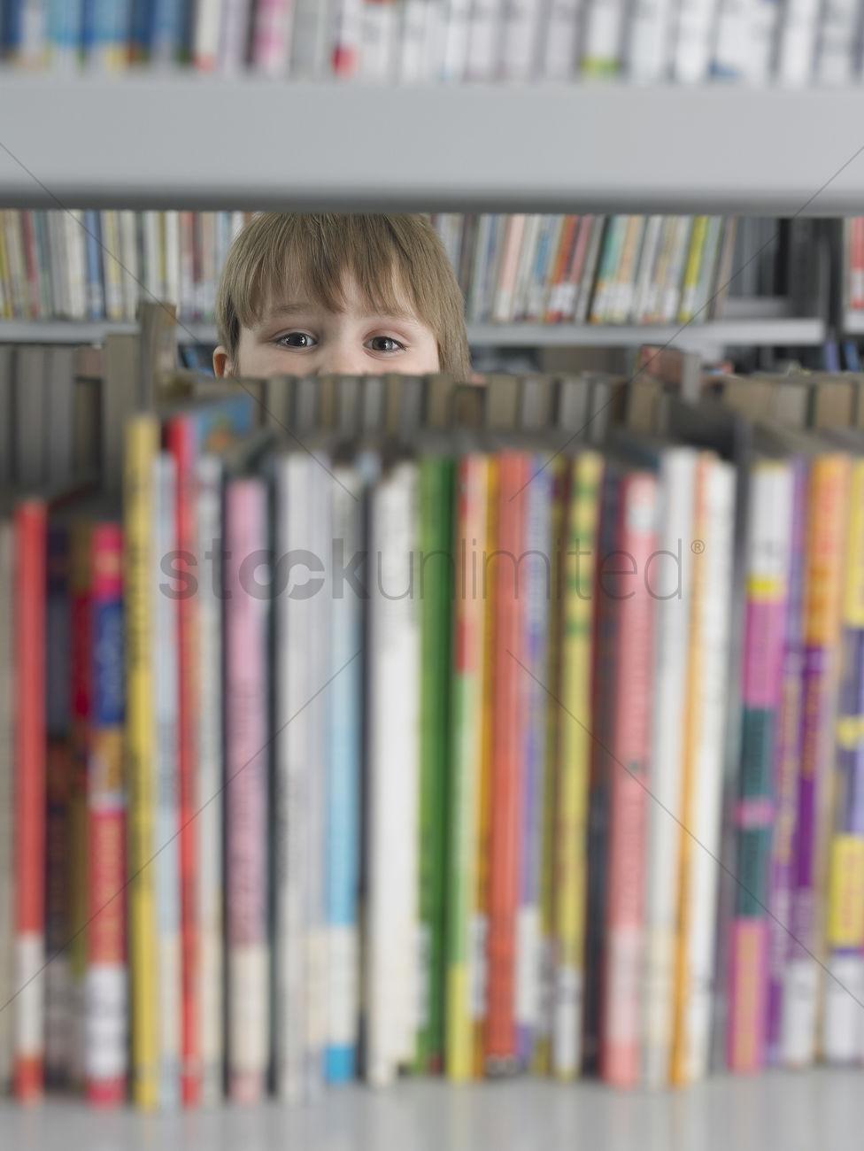 Boy Peeking From Behind Bookshelf In Library Stock Photo