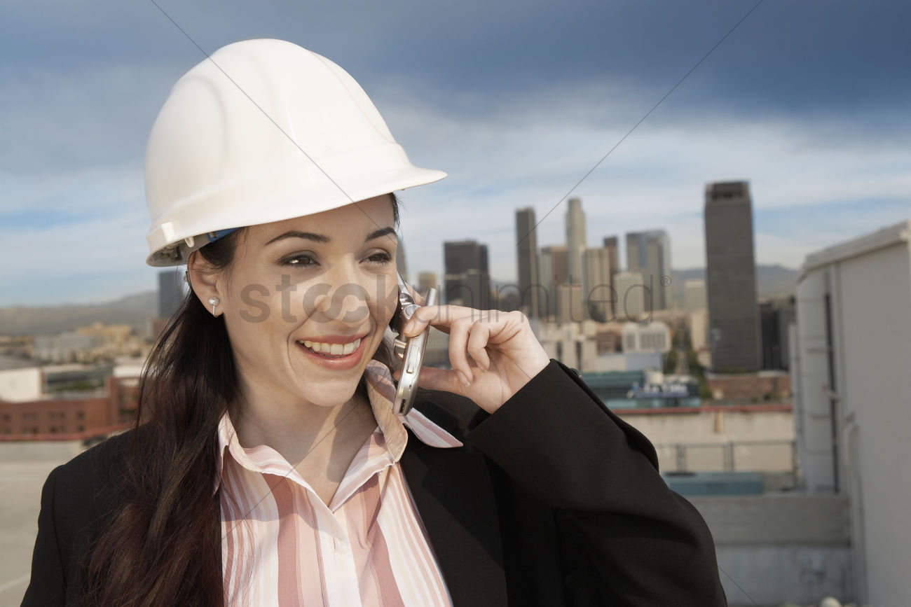 business woman in hard hat using mobile phone in city stock photo