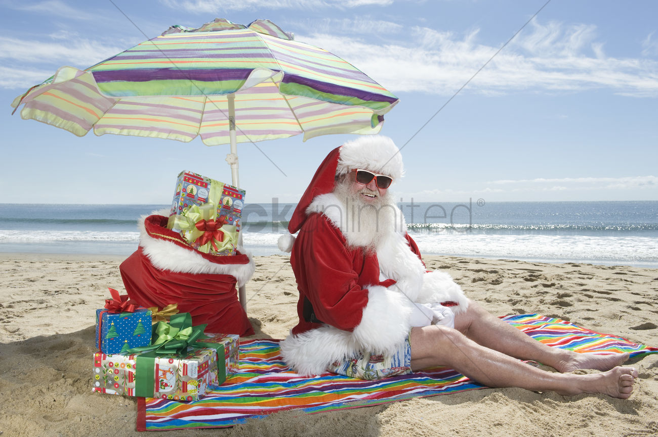 father christmas sits under a parasol on the beach stock photo