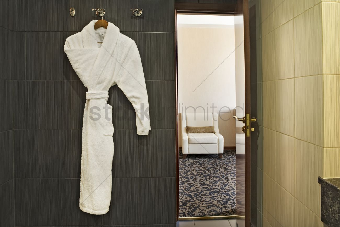 Interior of a hotel room with a white dressing gown hanging up and ...