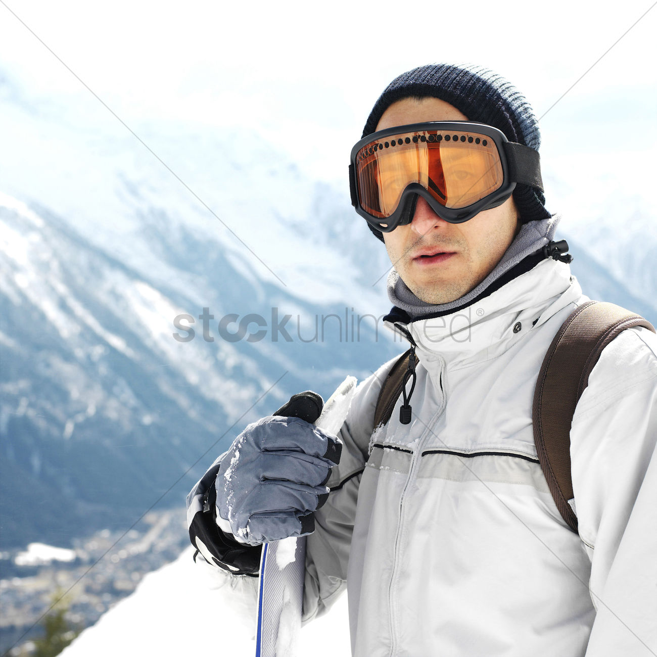 in warm clothing and ski goggles holding snowboard