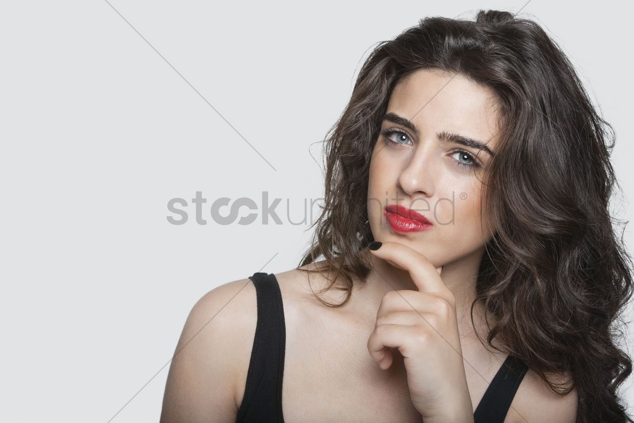 bf60dfac994a8 portrait of a thoughtful young woman with hand on chin over gray background  stock photo