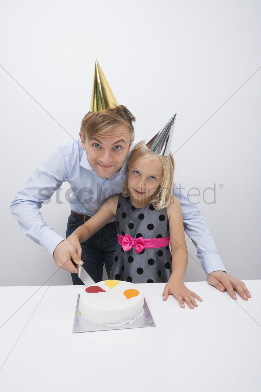 Portrait of father and daughter cutting birthday cake at table Stock