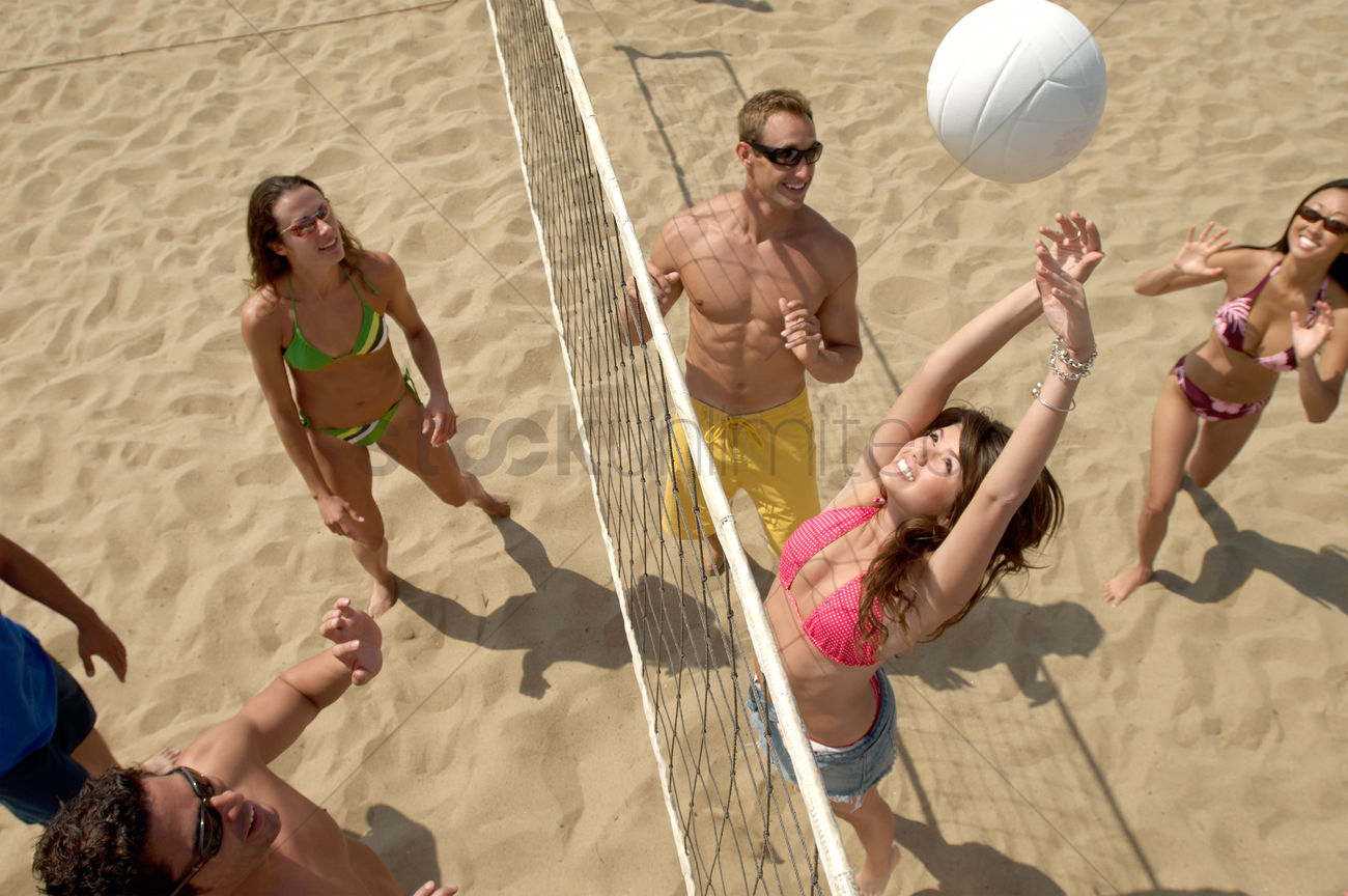 A Group Of Young People Play Beach Volleyball On A Weekend