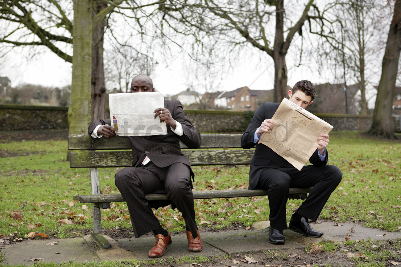 two businessmen reading newspaper on the bench stock photo - 1676330