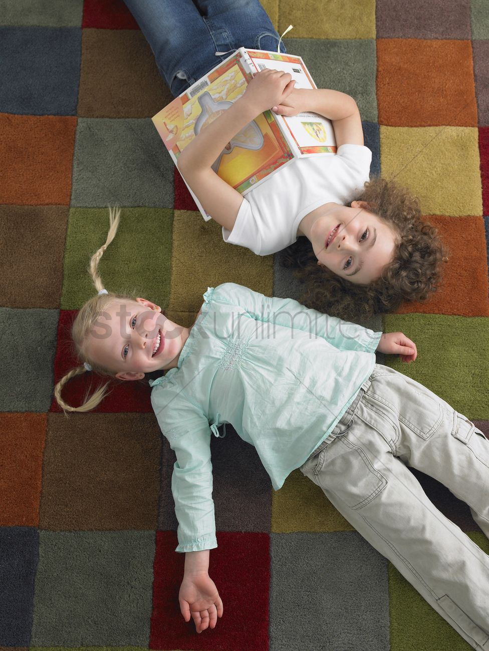 Two Girls Lying Down On Library Floor View From Above Stock