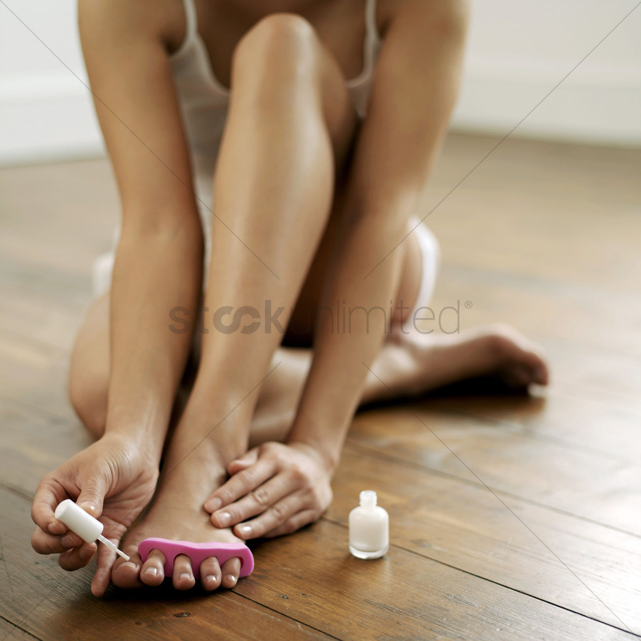 Woman Applying Nail Polish On Her Toe Nails Stock Photo 1699738