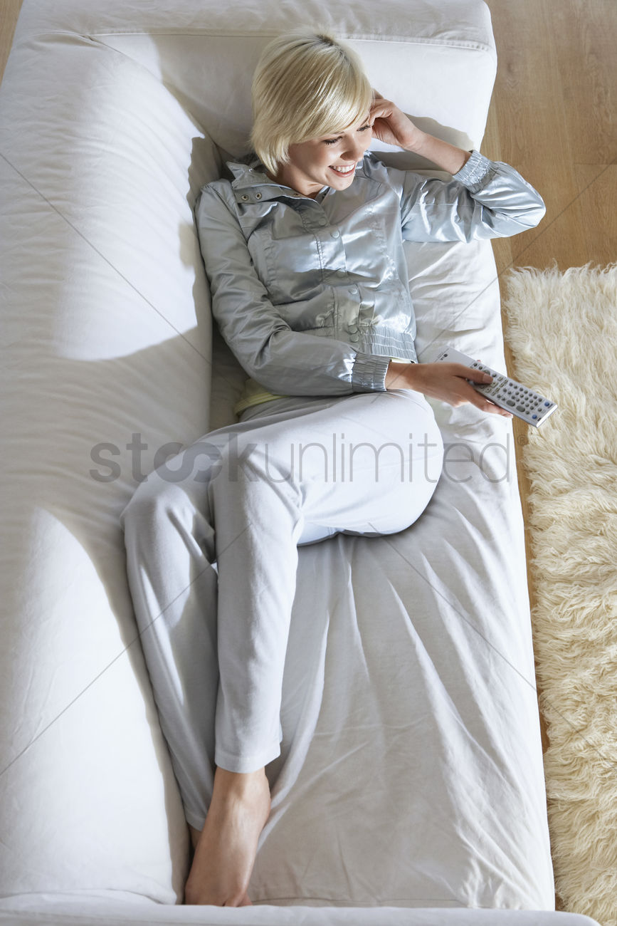 Woman Lying On Sofa Watching Television View From Above Stock Photo