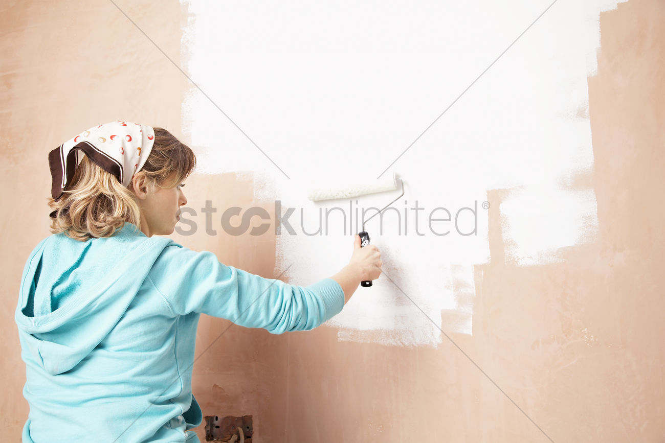 Woman Painting Interior Wall With Paint Roller Stock Photo