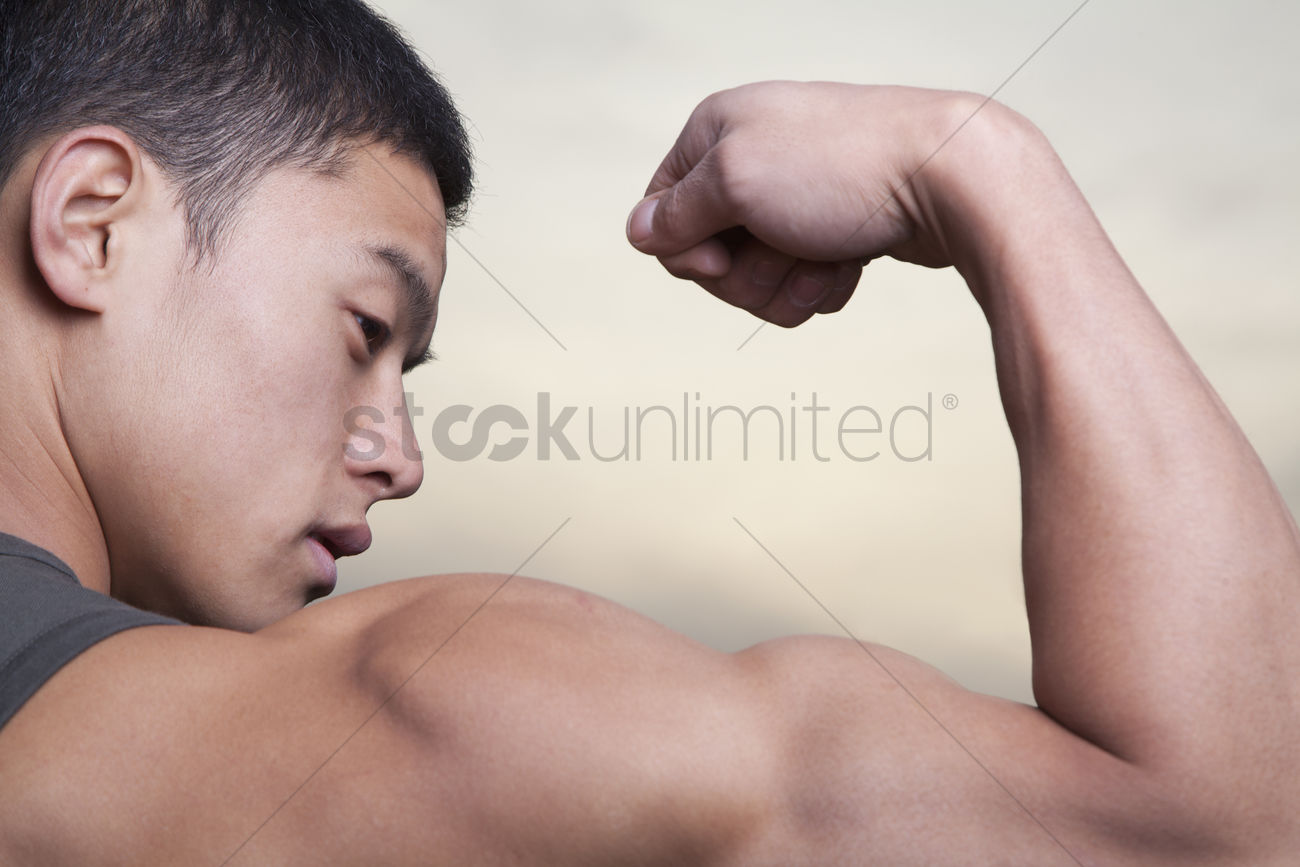 Young Man Showing Off His Bicep Muscles Stock Photo 2082906