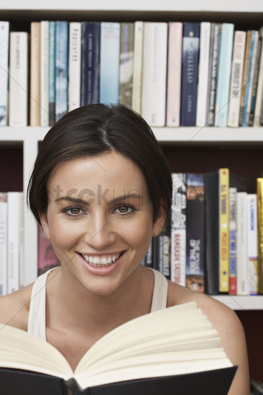 Young Woman Holding Book By Bookshelf Portrait Stock Photo