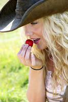 A woman with cowboy hat eating a strawberry