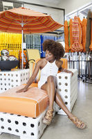African american woman sitting in arm chair at garden furniture store