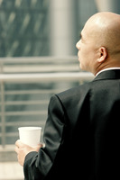 Back shot of a bald man in business suit holding a cup