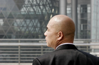 Back shot of a bald man in business suit looking to the side