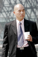 Bald man in business suit holding a cup