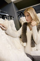 Beautiful blond woman looking at price tag of wedding gown in bridal boutique