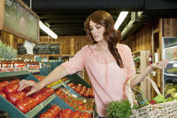 Beautiful brunette woman shopping for tomatoes in supermarket