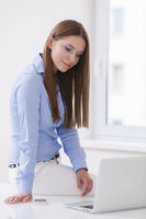 Beautiful businesswoman sitting on desk and looking at laptop
