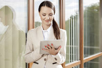 Beautiful businesswoman using digital tablet against office building