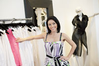 Beautiful mid adult woman standing by clothes rack in fashion boutique