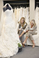 Beautiful young woman sitting with mother while looking at wedding gown in bridal store