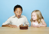 Boy and girl blowing the candle on a birthday cake