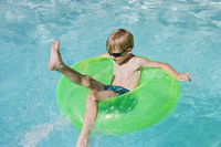 Boy on float tube in swimming pool