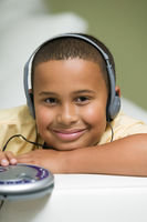 Boy on sofa listening to portable cd player portrait