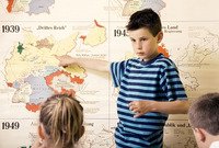 Boy pointing at a map while other kids watching