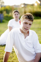 Popular : Boy sitting in the park with his mother in the background