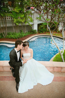 Bride and groom sitting on the edge of bride over the swimming pool