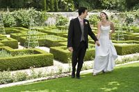 Bride and groom walking hand in hand in garden