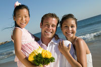 Bride and groom with flower girl at beach  portrait