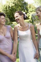 Bride with two women in garden holding hands smiling portrait