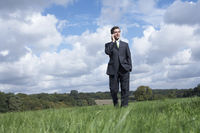 Business man talking on mobile phone in field