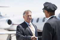 Businessman beside private jet shaking hands with pilot