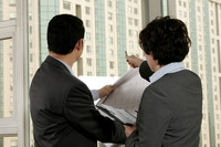 Businessman discussing a building plan with his assistant