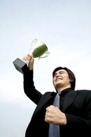 Businessman lifting up his trophy