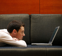 Businessman lying on the couch using laptop