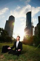 Businessman meditating in the park
