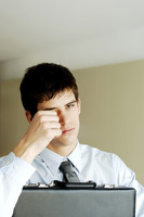Popular : Businessman rubbing his eye while hugging a briefcase