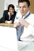 Businessman tying necktie while looking at laptop  wife in the background