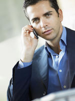 Businessman using cell phone indoors portrait